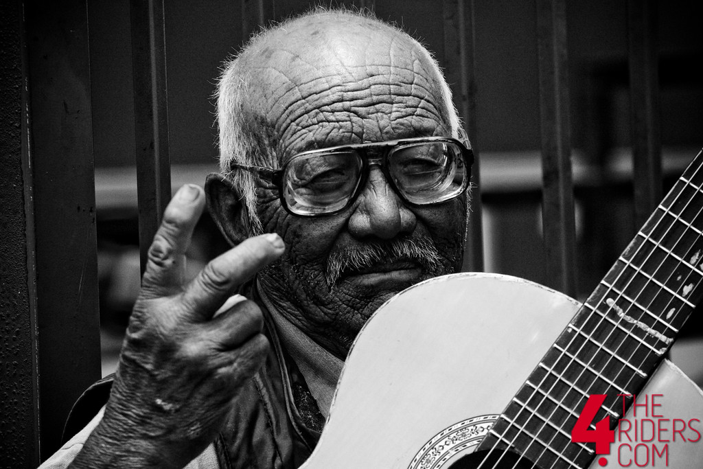 old man black and white peace sign guitar